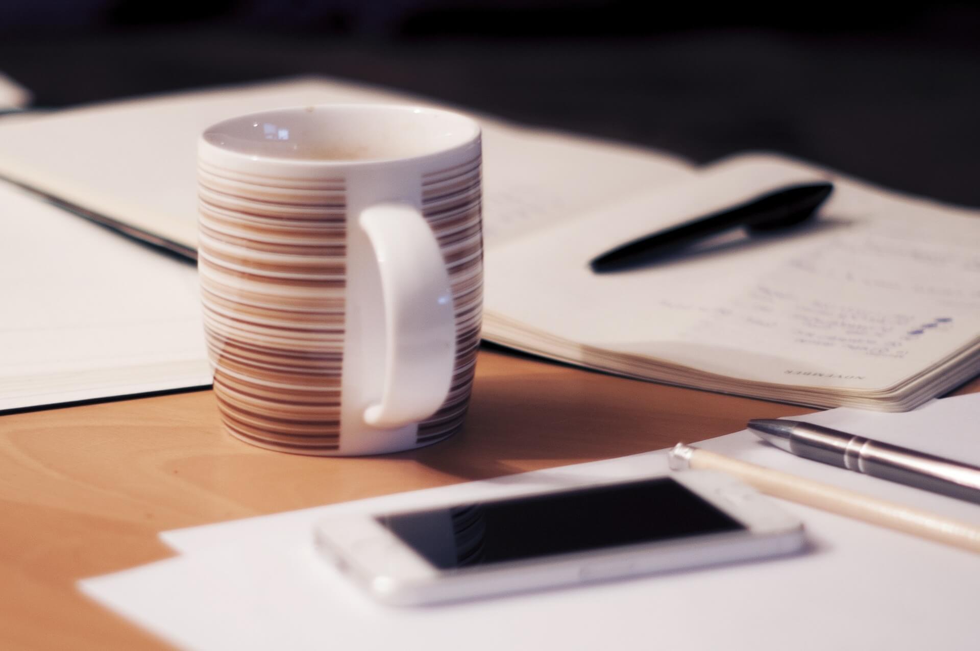 手帳とiPhoneとマグカップ
